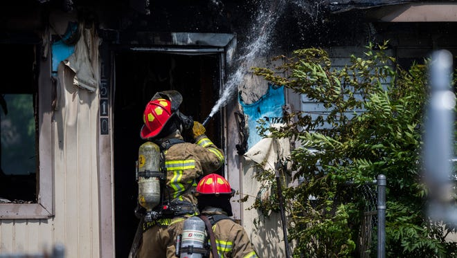 Firefighters extinguish a house fire on Monday, April 2, 2018 in the 1500 block of Trojan Drive.