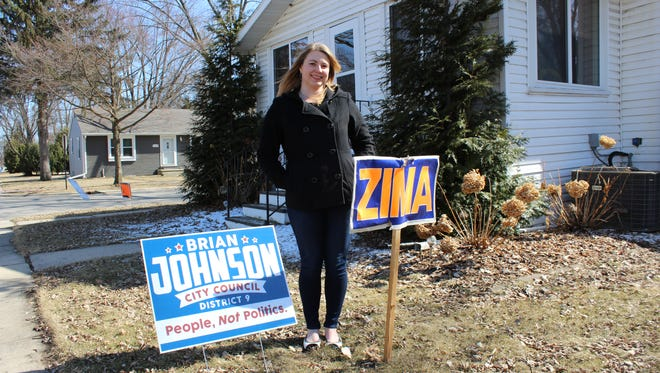 Kayla Jones stands in front of campaign signs for both Brian Johnson and Guy Zima at her home on Liberty Street on April 1, 2018.