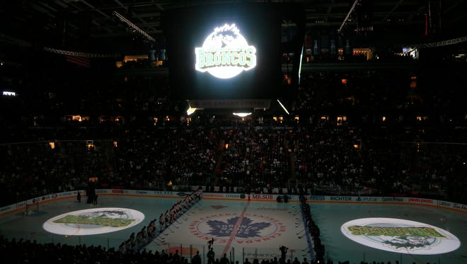 The logo of the Humboldt Broncos is displayed on the ice and scoreboard during a moment of silence in tribute to the team before a game between the Montreal Canadiens and Toronto Maple Leafs at the Air Canada Centre.