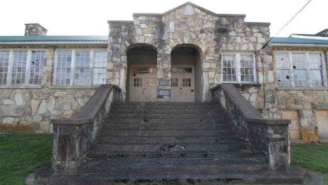 Issues with property lines surrounding the old Mars Hill High School have held up its sale by Madison County to real estate developers planning to transform the 1930's rock building into a 16-unit affordable housing complex.