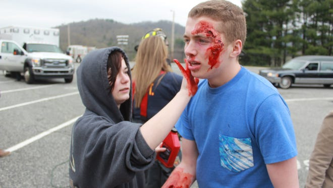 Madison High School junior Jessica Deaver applies fake blood around senior Coleson Garrett ahead of a reenactment of a drunk driving accident at Madison High School April 19.