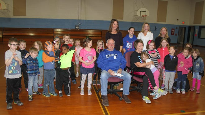 Pat (front row, in blue pullover) and Kathy Kellenberger are surrounded by Amana Elementary School kindergarten students as they were honored for volunteerism at the school with the Excellence in Education award.