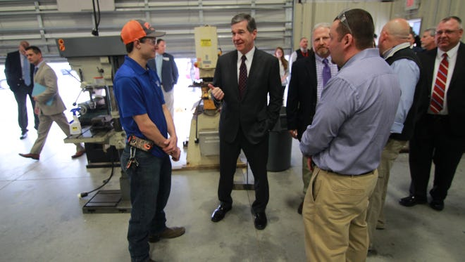 Governor Roy Cooper (center) speaks with Madison High School graduate and current Advanced Superabrasives employee Josh Bradley (left) inside the high school's advanced manufacturing center.