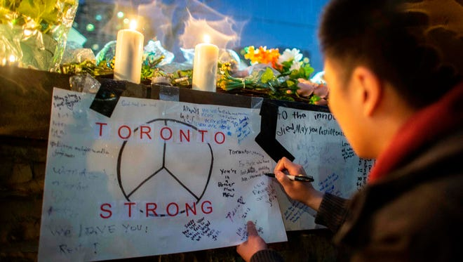 In this file photo taken on April 24, 2018 a mourner writes a message on a sign during a vigil in Toronto, Canada, near the site of the previous day's deadly street van attack.