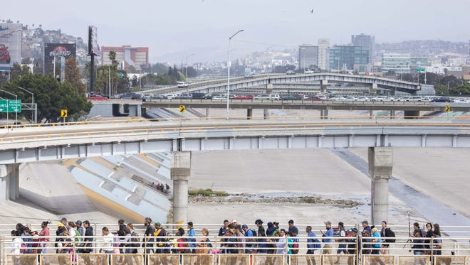 Central American part of the migrant caravan group crossing Tijuana bridge. Some gulping the food as much they can and some broke down crying just outside the entrance to the U.S. port at San Ysidro in Tijuana, on April 29, 2018. These migrants will decide whether to present themselves to U.S Border officers at the San Ysidro port of entry and apply for asylum.