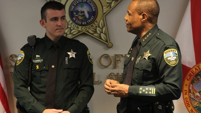 Leon County Sheriff's deputy Nicholas Kelly was recognized with the life-saving award for his work in pulling a woman from a car sinking into the Ochlockonee River Friday. To his right stands Sheriff Walt McNeil.