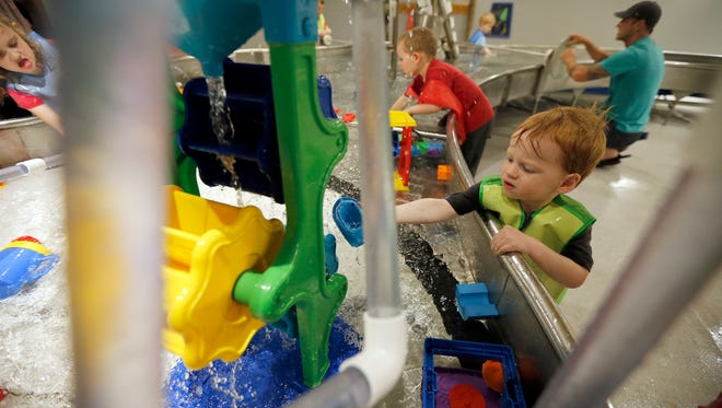 Caleb Foley, 23 months, of Colerain, plays in a the Water Works exhibit at the children's museum inside the Cincinnati Museum Center on Friday, May 4, 2018.