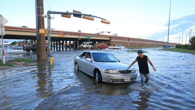 Steven Galindo walks around hid flooded car on Kostoryz Road on May 16, 2016.