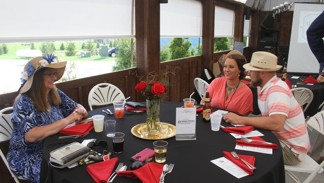 Discussing which horse they think will win the Kentucky Derby are, from left, Bonnie Clubb, Ashley Meek and Jordan Meek. All were in their best Kentucky Derby wear during the Williamsburg Area Chamber of Commerce Gala Saturday, May 5.