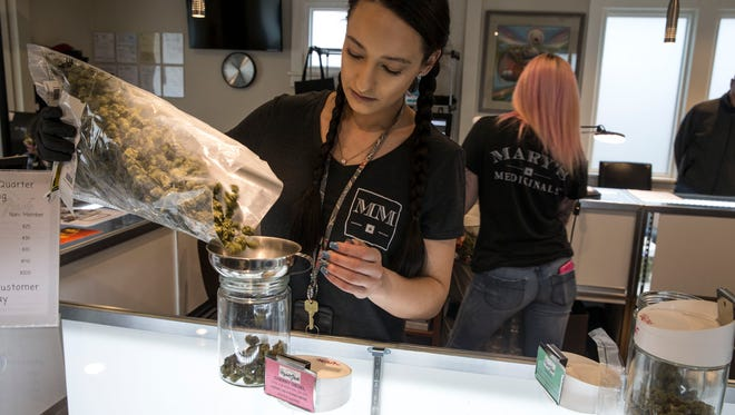 Raven Guillmette, store manager, measures out a strain of marijuana called Cherry Diesel. Higher Grade dispensary offers fine cannabis for medicinal purposes. 