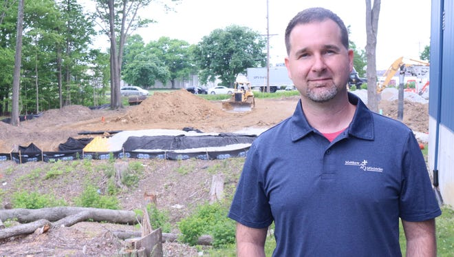 Matthew 25 Ministries CEO Tim Mettey in front of construction beginning on a $6 million expansion of the ministry's Blue Ash facilities.