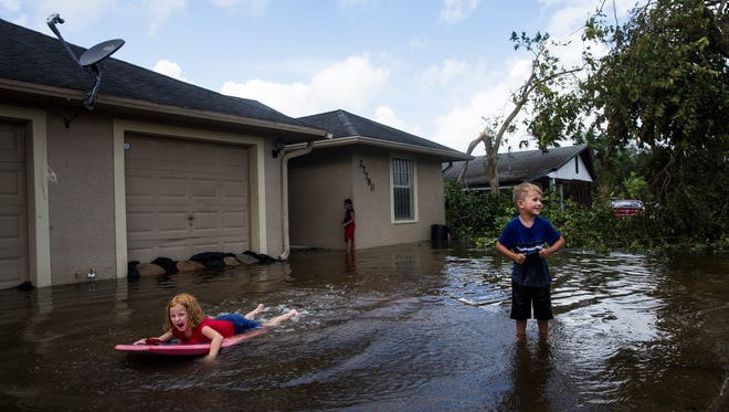 Julia Waters, 7, left, and Jayden Emmons, 4, play in their flooded driveway a day after Hurricane Irma passed through Bonita Springs on Monday, Sept. 11, 2017.
