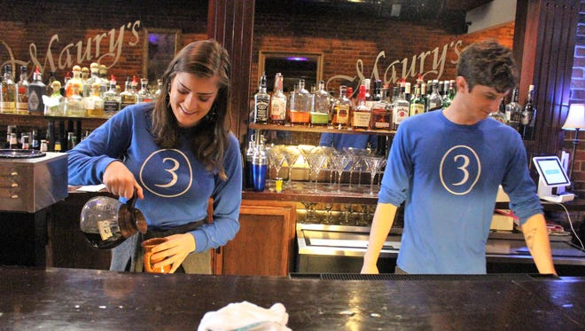 Lily Johnston and Joel Roberts clean the bar at Tres on Friday. The downtown eatery faces an uncertain future after an investor pulled out last month.