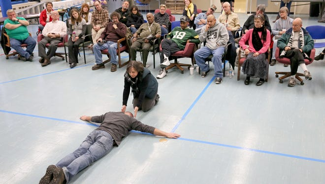 During a 2014 Feast of Crispian workshop at the Milwaukee VA Hospital, actor Rich Gillard (foreground) performs with Air Force veteran Kathleen O'Brien (kneeling) of San Diego.  The pair silently acted out a Shakespeare-inspired series of movements.