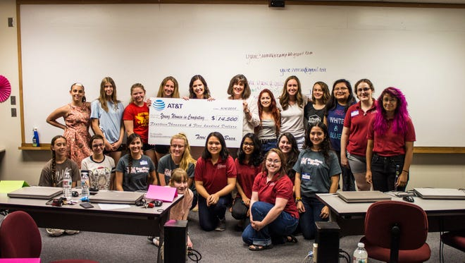 Surrounded by students who participate in the annual YWiC summer camp, Terri Nikole Baca from AT&T presents Leslie Cervantes from the New Mexico State University Foundation with a check worth $14,550 that supports YWiC's creation of a new camp for female high school seniors who will attend NMSU.
