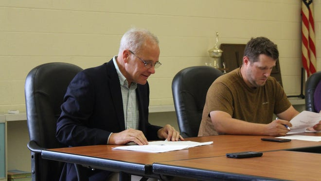 Brian White, left, a member of the Lexington facilities finance committee, speaks with the Lexington school board Wednesday, June 27, 2018. Board member Rob Schuster sits next to him.