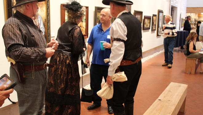 Color characters talking to an artist at opening night of the American Great Plains Art Exhibit Thursday, June 28, 2018 at the Quartermaster building.