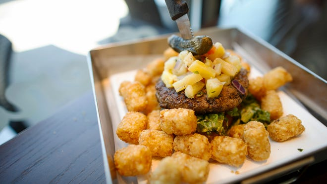 An open faced beef burger with a side of tots at Frenchie Fresh in the Oakley neighborhood of Cincinnati on Friday, June 29, 2018.