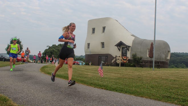 Katarina MacMillan of Manchester runs past the race's namesake inthe Shoe House 5-miler early in the morning on Wednesday, July 4, 2018.