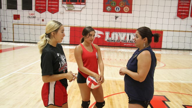 Left to right: Loving seniors Chasity Onsurez and Anyssa Rodriguez talk with new head coach Raquel Chacon after Thursday's practice. Chacon was named the new varsity volleyball coach on Tuesday.