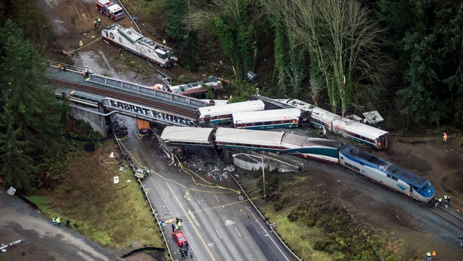In this Dec. 18, 2017 file photo, cars from an Amtrak train that derailed lie spilled in DuPont. Federal investigators are hearing from witnesses as they look into last year's Amtrak train derailment south of Seattle, Wash., that killed three people and injured dozens. (Bettina Hansen/The Seattle Times via AP, File)