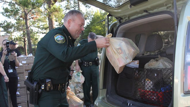 Former LCSO Department of Investigations Chief Jeff Beasley loads bags into the back of a vehicle at a Farm Share event.