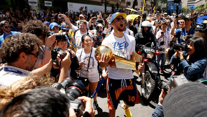 Golden State Warriors guard Stephen Curry holds onto the Larry O'Brien Championship Trophy during the Warriors 2018 championship victory parade in downtown Oakland.