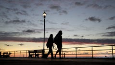 Two people walk the Asbury Park boardwalk and watch