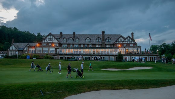 With the lights of clubhouse glowing, competitors walk
