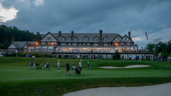With the lights of clubhouse glowing, competitors walk up the 18 fairway during the second round of stroke play of the 2018 U.S. Junior Amateur at Baltusrol Golf Club in Springfield, N.J. on Tuesday, July 17, 2018.