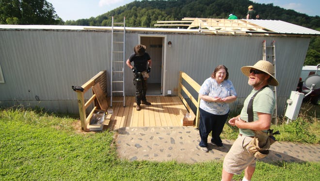 Shelia Whittington talks with Jake Owen of the Community Housing Coalition of Madison County as volunteer crews complete repairs to Whittington's home.