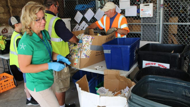 Calhoun County's Solid Waste and Recycling Coordinator Sarah Kelly at the Marshall Recycling Center sorts through some office paper with staff and volunteers.