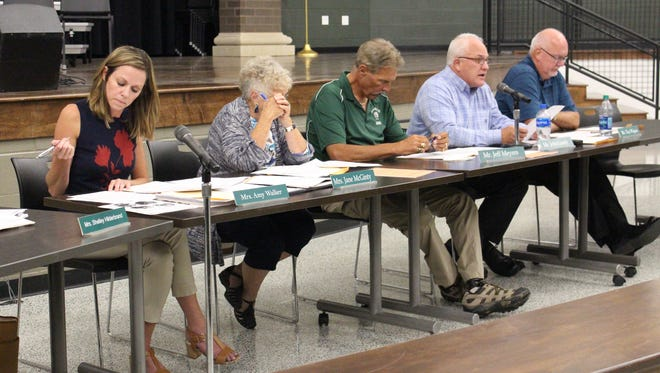 Board member John Luedy, second from right, reads a contingency plan the Madison school board approved Wednesday. The plan was part of the board's approval of a contract with a company that will provide a STEM curriculum this school year.