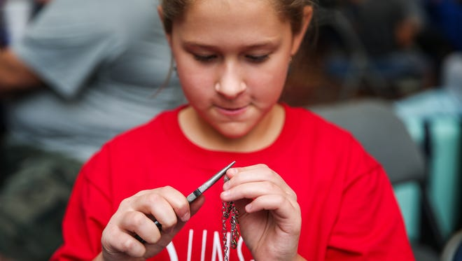 Olivia Hoelscher works on jewelry in her booth during the Kids, Inc. Business Showcase Saturday, July 28, 2018, at the Sunset Mall.