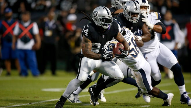 Oakland Raiders running back Marshawn Lynch (24) runs for a touchdown against the Los Angeles Rams in the first quarter at Oakland Coliseum.