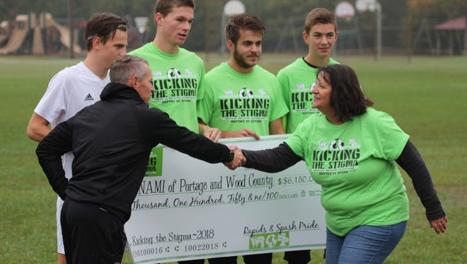 SPASH boys soccer coach Derek Bell shakes hands with Linda Froehlich of the National Alliance on Mental Illness for Portage and Wood counties. Players from Wisconsin Rapids and SPASH presented a check for $6,150 on Oct. 5 as part of the Kicking the Stigma Mental Health Awareness Campaign.