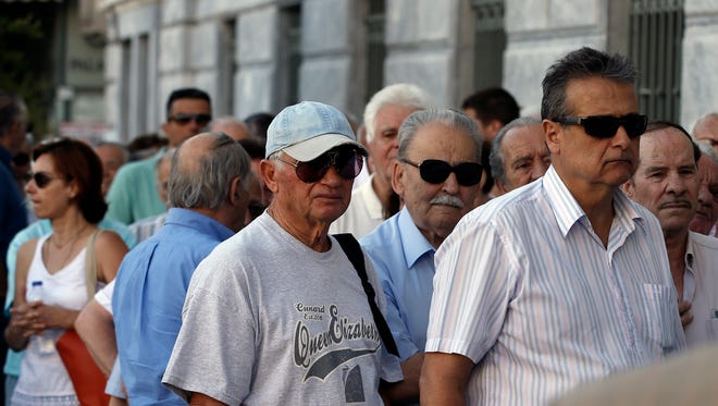 The first customers, most of them pensioners, stand in a queue to enter a branch at National Bank of Greece headquarters in Athens, Monday, July 20, 2015. Greek banks reopen on Monday morning, but many restrictions on transactions, including cash withdrawals, will remain. Also, many goods and services will become more expensive as a result of a rise in Value Added Tax approved by Parliament last Thursday, among the first batch of austerity measures demanded by Greece's creditors.