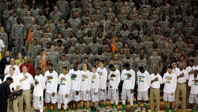Oregon's players listen to national anthems with U.S. Army personnel before last year's Armed Forces Classic game against Georgetown .