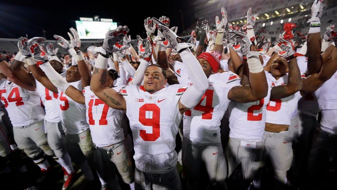 "Ohio State receiver Devin Smith (9) and teammates sing ""Carmen Ohio"" after they defeated Michigan State, 49-37, Saturday in East Lansing."