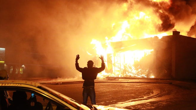 """A protester poses for a """"hands up"""" photo Nov. 24 in front of a burning building on West Florissant Avenue in Ferguson, Mo. 'Hands Up, Don't Shoot' has become a rallying cry despite questions whether Michael Brown's hands were raised in surrender before being fatally shot by a Ferguson police officer."""