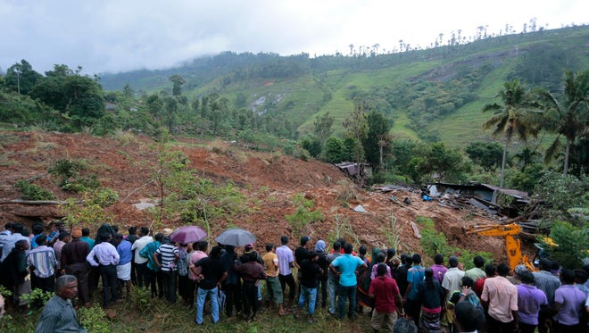 A crowd gathers to watch rescue operation at the site of a mudslide.
