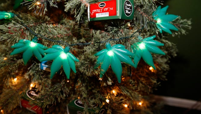 In this photograph taken on Thursday, Nov. 20, 2014, plastic marijuna leaves light a Christmas tree as part of holiday display in a recreational marijuana shop in northwest Denver.