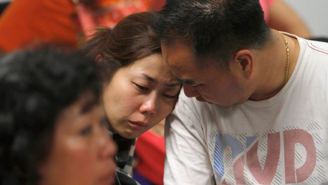 A relative of the passengers of AirAsia flight QZ8501 weeps as she waits for the latest news on the missing jetliner at a crisis center set up by local authority at Juanda International Airport in Surabaya, East Java, Indonesia, Sunday, Dec. 28, 2014.