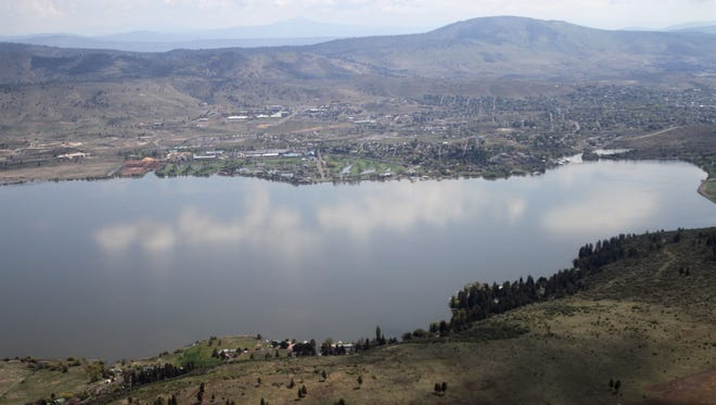 This May 7 photo shows Klamath Falls on the far side of Upper Klamath Lake. Tens of thousands of acres in the Klamath Basin will go without water this summer. AP FILE - This May 7, 2013 file photo shows Klamath Falls, Ore., top, on the far side of Upper Klamath Lake. Tens of thousands of acres in Oregon's drought-stricken Klamath Basin will have to go without irrigation water this summer after the Klamath Tribes and the federal government exercised for the first time newly confirmed powers that put the American Indian tribes in the driver's seat over the use of water.  (AP Photo/The Herald and News, Steven Silton)