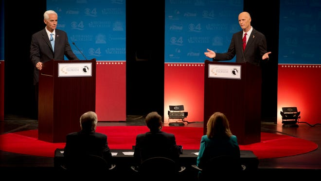 Democratic challenger, former Republican Gov. Charlie Crist, left, and Florida Republican Gov. Rick Scott, answer questions during their second debate, Wednesday, Oct. 15, 2014 in Davie, Fla. It was sponsored by the Florida Press Association and Leadership Florida. (AP Photo/Wilfredo Lee, Pool)