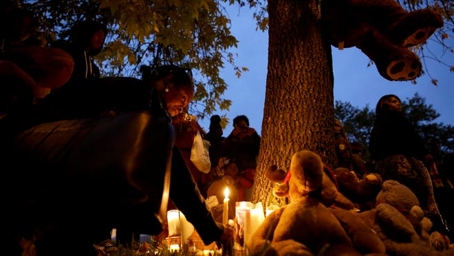 A woman places a candle at a memorial to Vonderrit  Myers on Oct. 9 in St. Louis.  Myers was shot Wednesday by a St. Louis police officer.