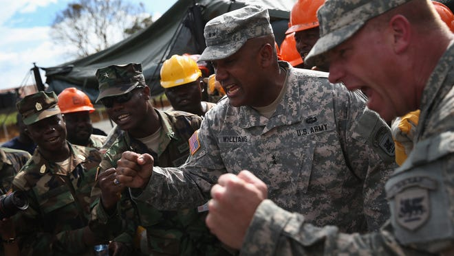 Liberian Brig. Gen. Daniel Ziankhan, chief of staff for the Armed Forces of Liberia, left, and American Maj. Gen. Darryl Williams, commander of U.S. Army Africa, cheer at the construction site of an Ebola treatment center Oct. 15 in Tubmanburg, Liberia.