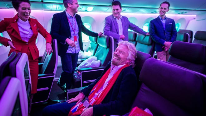 Virgin Atlantic founder Sir Richard Branson shares a laugh with Virgin Atlantic executives and flight crew at a special event showing off the carrier's first-ever Boeing 787 Dreamliner in Atlanta on Oct. 24, 2014.