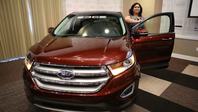 Cristina Aquino, a Ford marketing manager, poses with the new 2015 Ford Edge in Irvine, Calif.