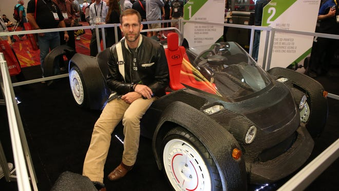 """John """"Jay"""" Rogers from Local Motors in Phoenix shows off their 3-D printed car at the SEMA show in Las Vegas."""
